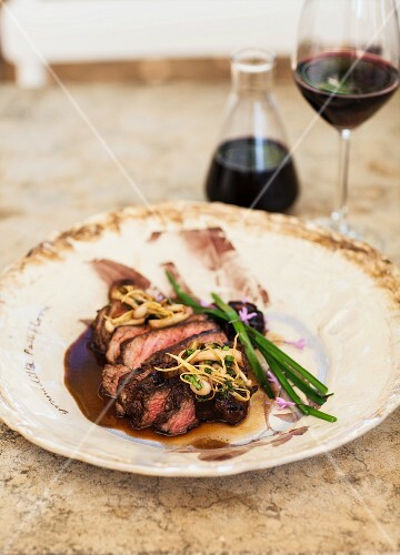 Sliced beef fillet on a plate with a carafe and a glass of wine in the background
