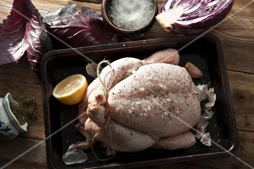 A raw chicken ready to roast with garlic, oregano, sea salt and lemon