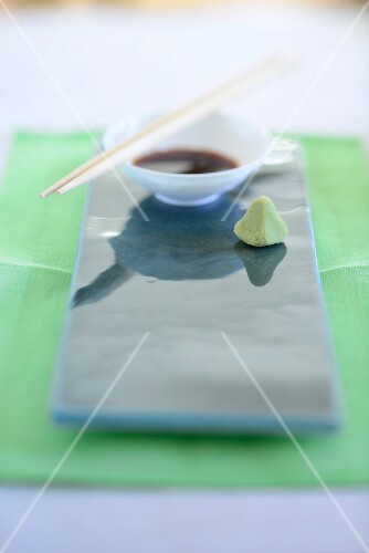 Soy sauce and wasabi paste on a shiny ceramic platter