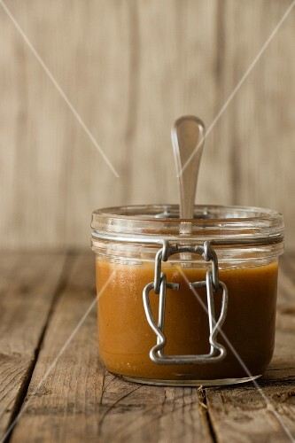 Dulce de leche in a flip-top jar with a spoon
