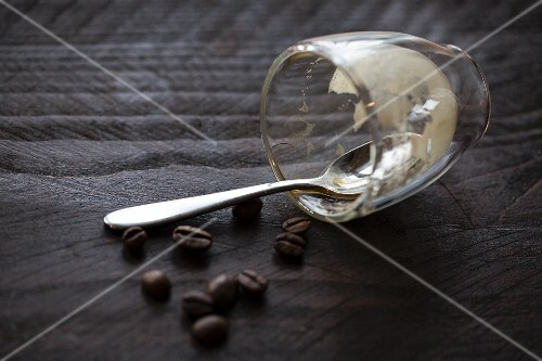 An empty espresso glass with a spoon and coffee beans on a wooden table