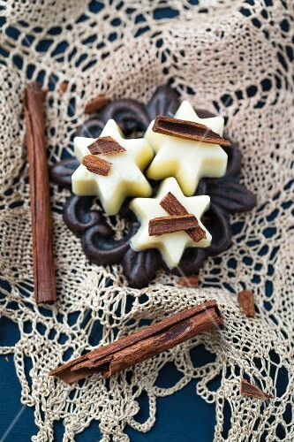 White chocolate pralines with cinnamon sticks on a crocheted doily