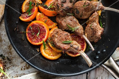 Roasted lamb chops with slices of blood orange and herbs in a pan