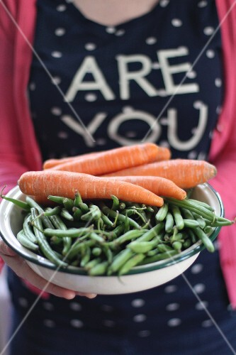 A woman holding a bowl of green beans and carrots