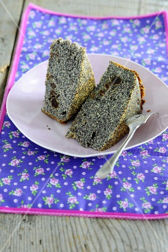 Two slices of poppyseed cake on a plate with a fork