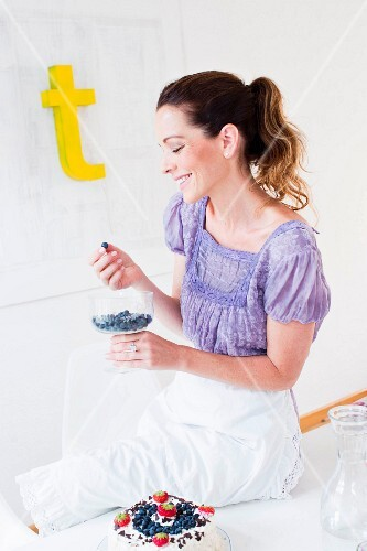 A woman eating blueberries from a glass bowl