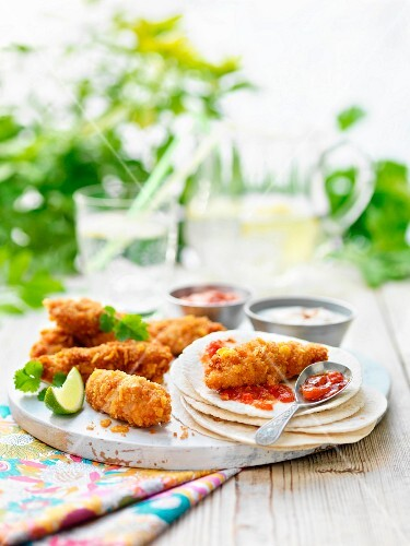 Mini crispy chicken fajitas and tortilla wraps with limes and tomato relish on a garden table