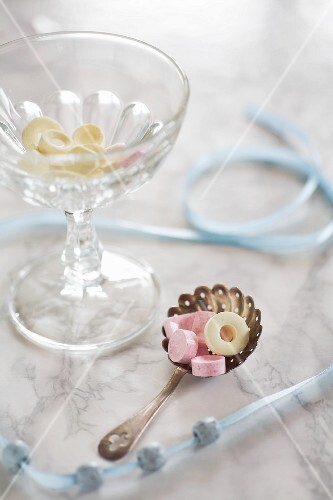 An arrangement featuring a beaded ribbon and sweets in a glass bowl and on a silver spoon