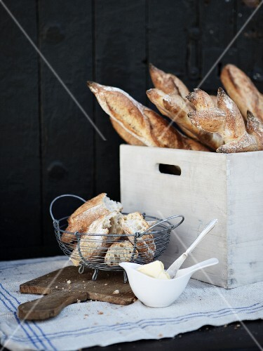 Fresh baguettes and a wooden crates and in a wire basket