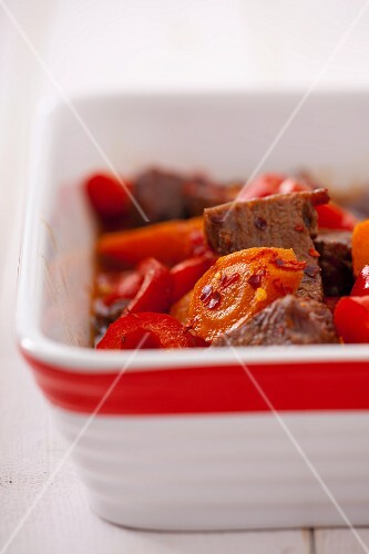 Beef with peppers and chilli flakes in a baking dish