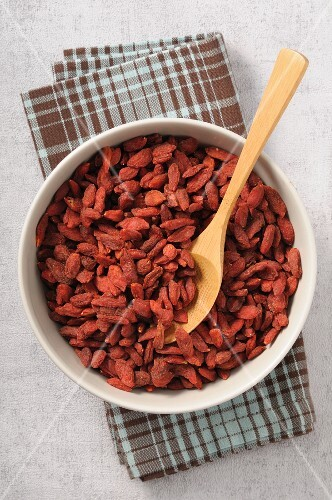 Dried gojiberries in a bowl with a wooden spoon