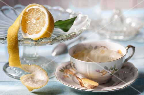 A cup of herbal tea with ginger and lemons
