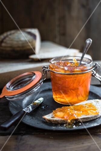 Orange marmalade in a flip-top jar and on a slice of bread