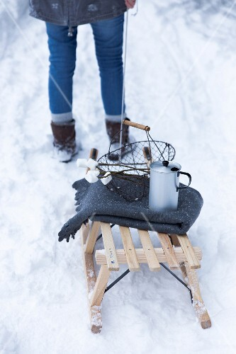 A woman pulling a sledge with a jug and marshmallows through the snow