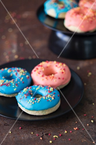 Blue and pink glazed doughnuts with sugar sprinkles on a plate