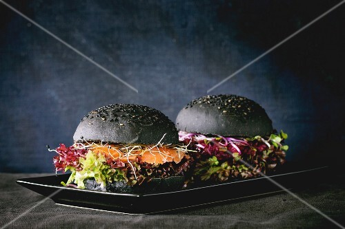 Two homemade black burgers with salmon, beetroot, sprouts and lettuce