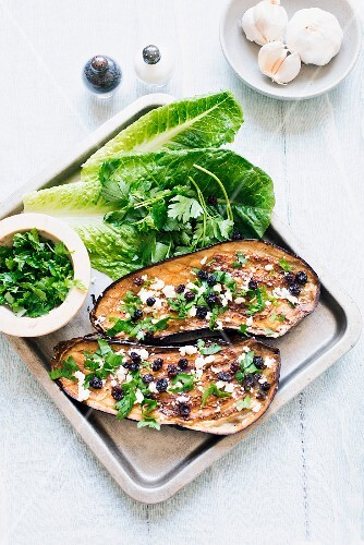 Baked aubergines with garlic, cheese, parsley and raisins