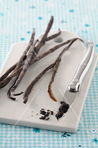 Vanilla pods and a knife with vanilla seeds on a chopping board