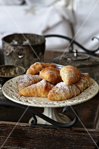 Mini croissants on a vintage cake plate on a wooden tray with decorations