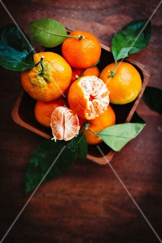 Mandarins with leaves on a rustic wooden surface