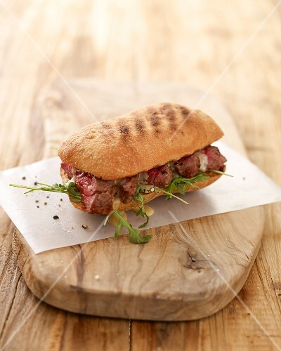 A steak sandwich with rocket on a wooden chopping board