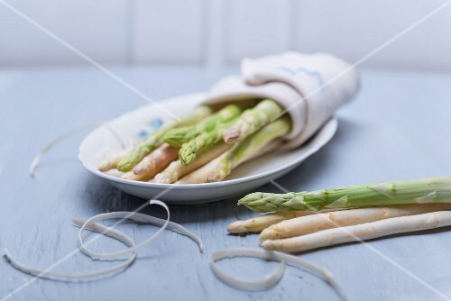 Green and white asparagus wrapped in a tea towel on a porcelain plate