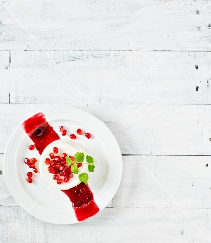 Panna cotta with a pomegranate sauce and pomegranate seeds