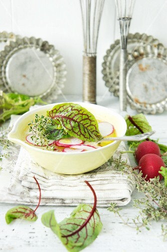 Radish leaf soup garnished with radishes, thyme and lettuce