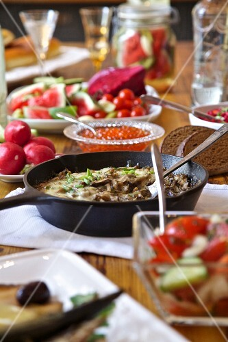 A table laid with Russian food including pickled vegetables, mushrooms and vodka