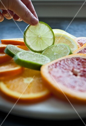 A woman taking a slice of lime from a tray of citrus fruit slices