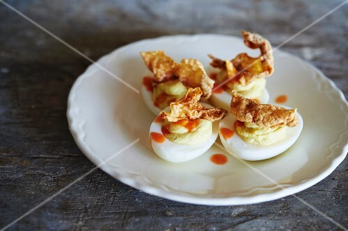Devilled eggs with hot sauce and pork scratchings
