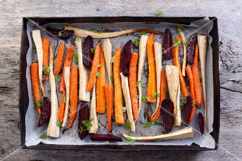 Roasted root vegetables and beetroot on a baking tray (seen from above)
