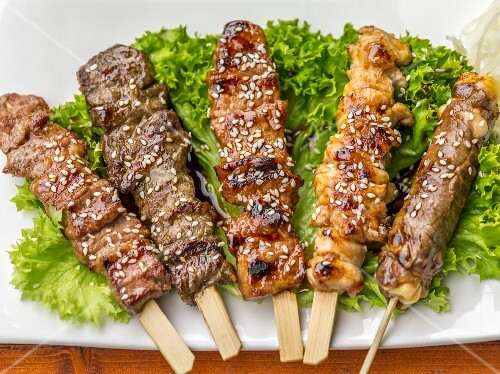 Grilled skewers with sesames seeds on lettuce leaves