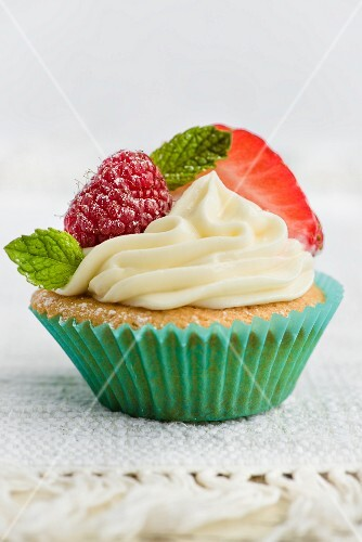A cupcake decorated with berries and mint