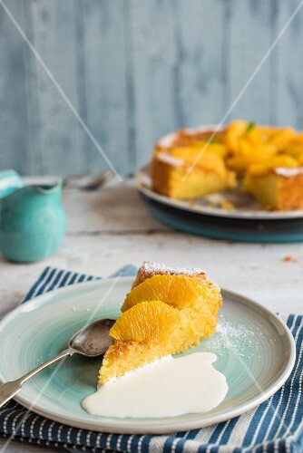 A slice of orange cake with cream