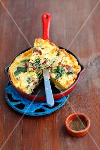 A pasta omelette with spinach and salami