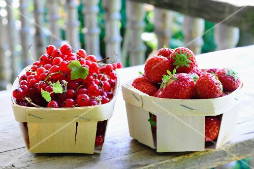 Redcurrants and strawberries in wooden baskets on a wooden table