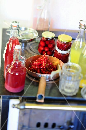 Various homemade fruit juices, preserved fruit and fresh redcurrants on an old stove