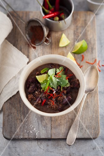 Chilli con carne with herbs on a wooden board