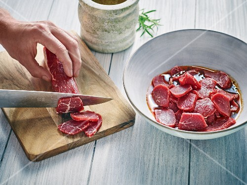 Sliced frozen meat being marinated