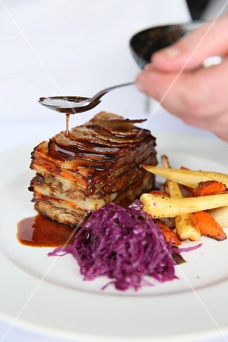 Layered lamb shoulder with potatoes served with red cabbage and root vegetables