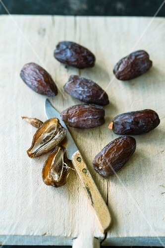 Fresh dates on a wooden board with a knife