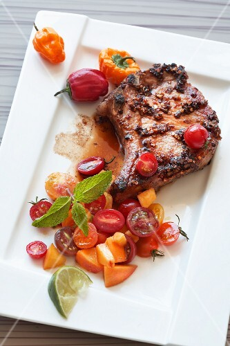 A pork chop with tomato salsa, peaches and peppers
