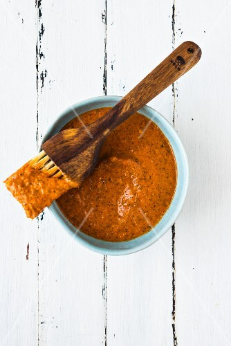 Harissa sauce in a blue bowl with a brush