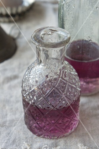 Homemade violet syrup in a carafe