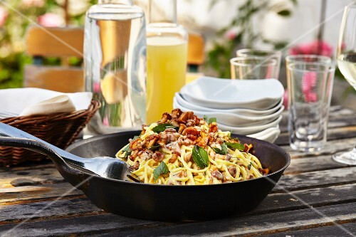 Spaghetti with chanterelle mushrooms in a pan on a garden table