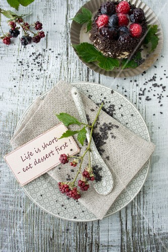 Place setting decorated with blackberries and chocolate caviar