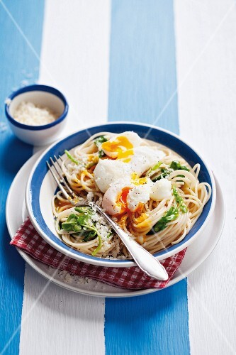 Spaghetti with poached eggs, Parmesan cheese and watercress