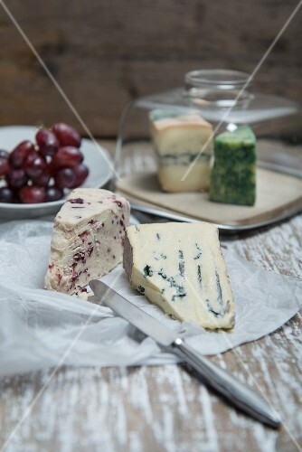Cambozola and Wensleydale cheese on a piece of paper with a cheese board and grapes in the background