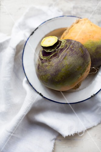 Organic turnips on an enamel plate on a linen cloth